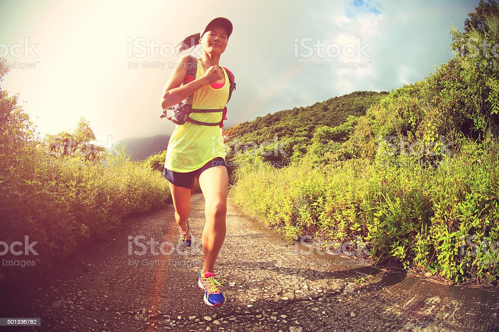 young fitness woman runner running on mountain trail stock photo
