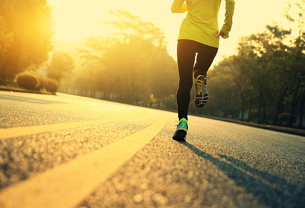 young fitness woman runner running on road - dedication stock photos and pictures