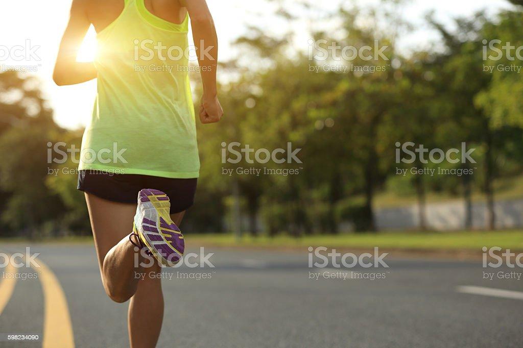 Jovem aptidão mulher de corredor correndo na estrada foto royalty-free