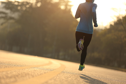 istock Young fitness woman runner running on sunrise road 1156227790