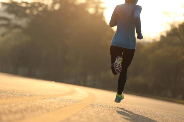 junge fitness-läuferin läuft auf sonnenaufgangsstraße - joggerin stock-fotos und bilder