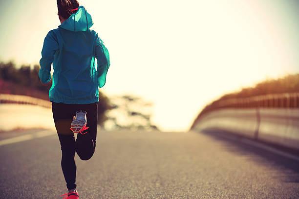 junge eignung frau läufer laufen auf sonnenaufgang straße - joggerin stock-fotos und bilder