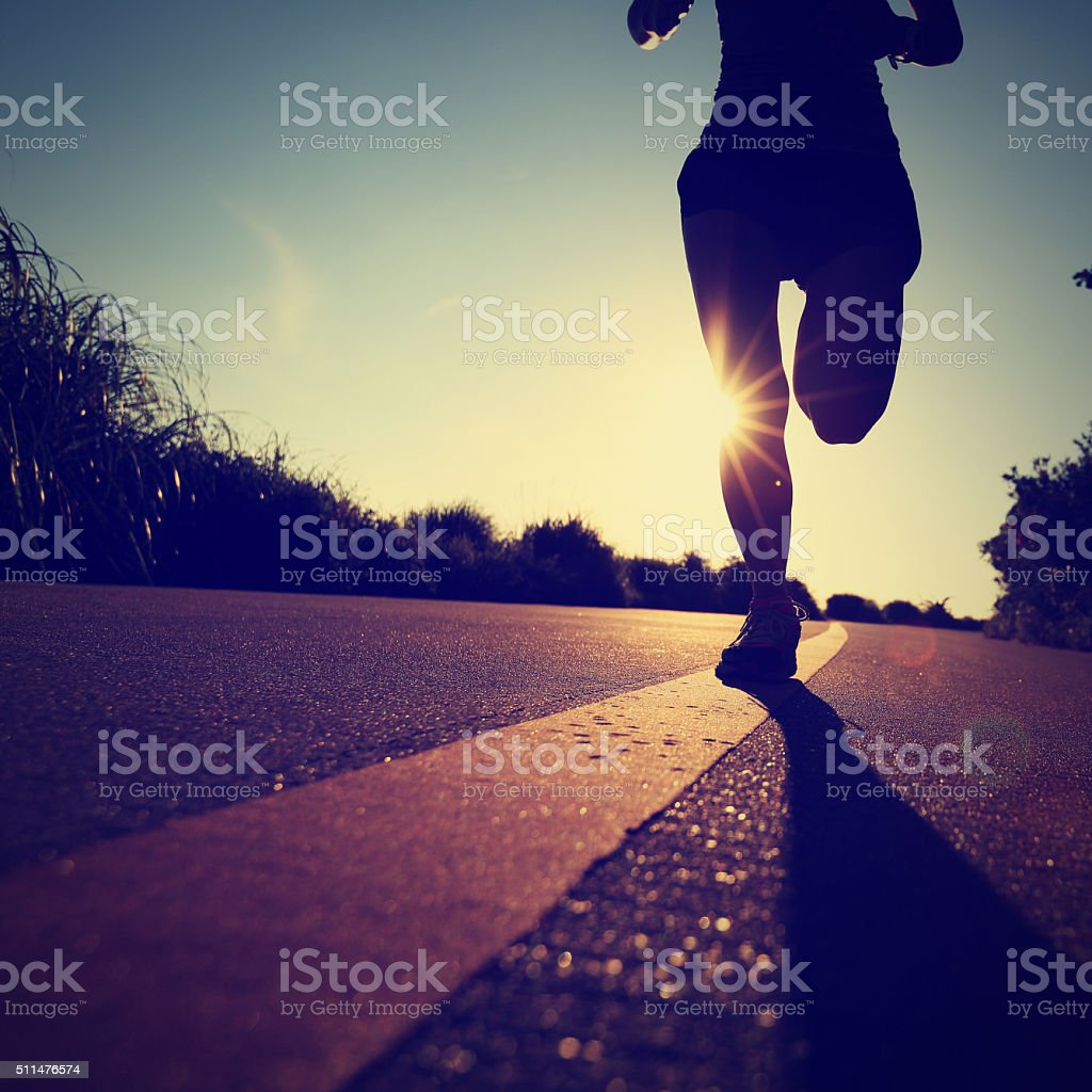 young fitness woman runner running on sunrise seaside road stock photo