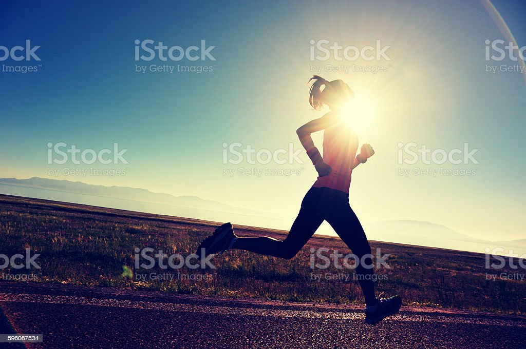 young fitness woman runner running on sunrise seaside trail royalty-free stock photo