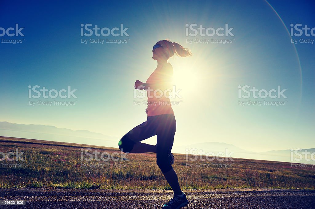 young fitness woman runner running on sunrise seaside trail foto royalty-free
