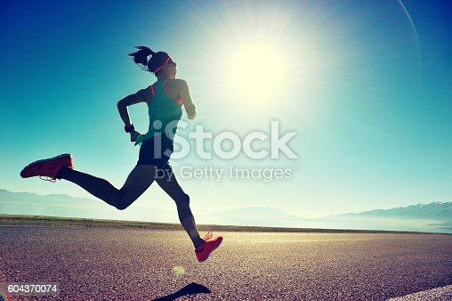 istock young fitness woman runner running on sunrise seaside trail 604370074