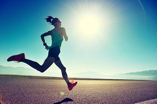 young fitness woman runner running on sunrise seaside trail stock photo