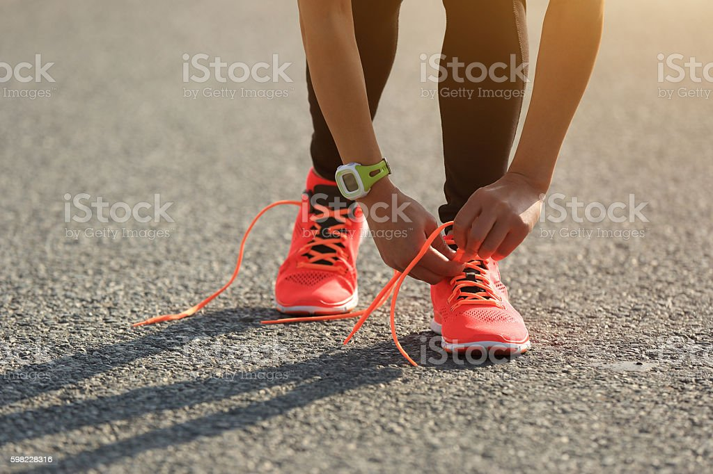 young fitness woman runner tying shoelace on road foto royalty-free
