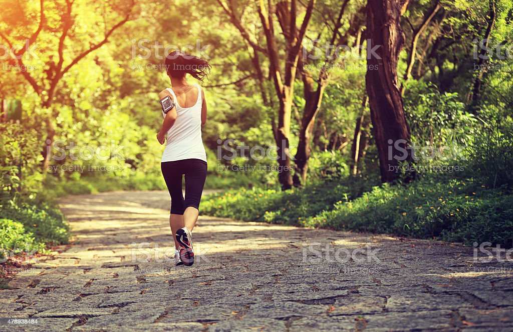 young fitness woman running at forest stone trail stock photo