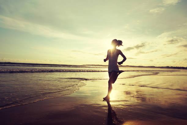 Junge Fitness-Frau läuft am Sonnenaufgang Strand – Foto