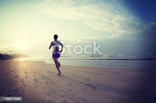 174919648istockphoto Young fitness woman running at sunrise beach 1166013581