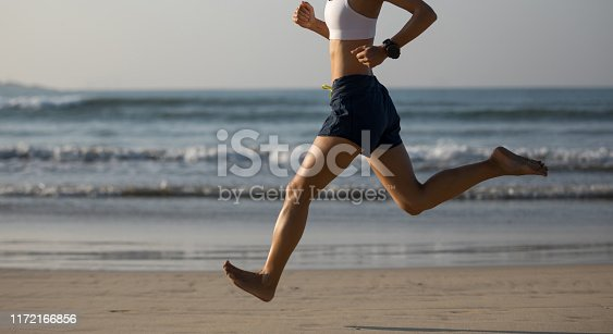 174919648istockphoto Young fitness woman running at sunrise beach 1172166856