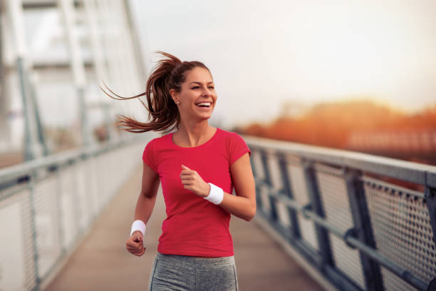 Young fitness woman running in the city stock photo