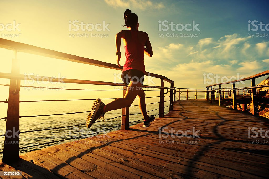 young fitness woman running on seaside wooden boardwalk stock photo