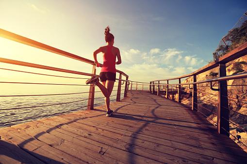 young fitness woman running on seaside wooden boardwalk