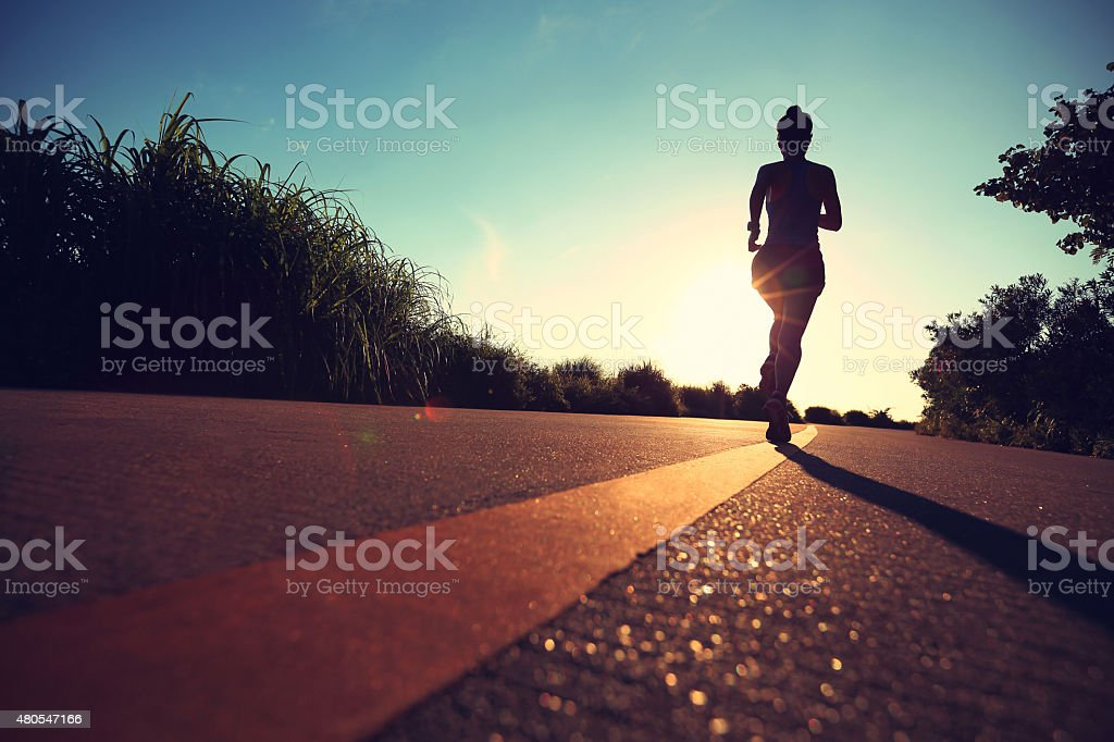 young fitness woman running on sunrise seaside trail stock photo