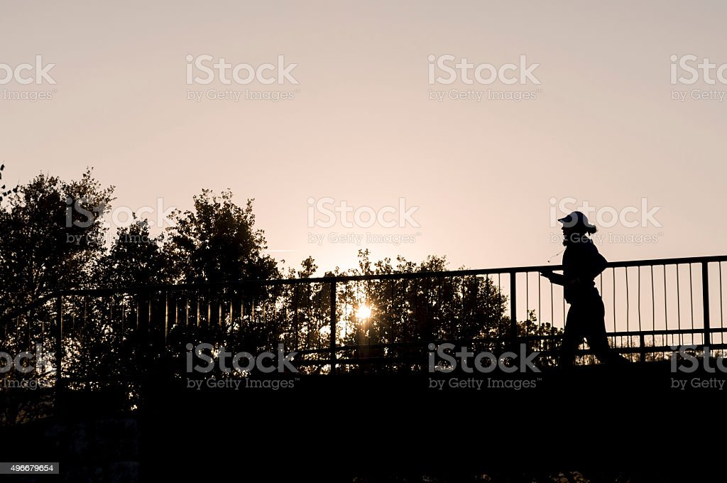 Young fitness woman running on the bridge It's a silhouette of a girl running on the bridge. She is determined to finish running before the sun goes down on a cold autumn day. 2015 Stock Photo