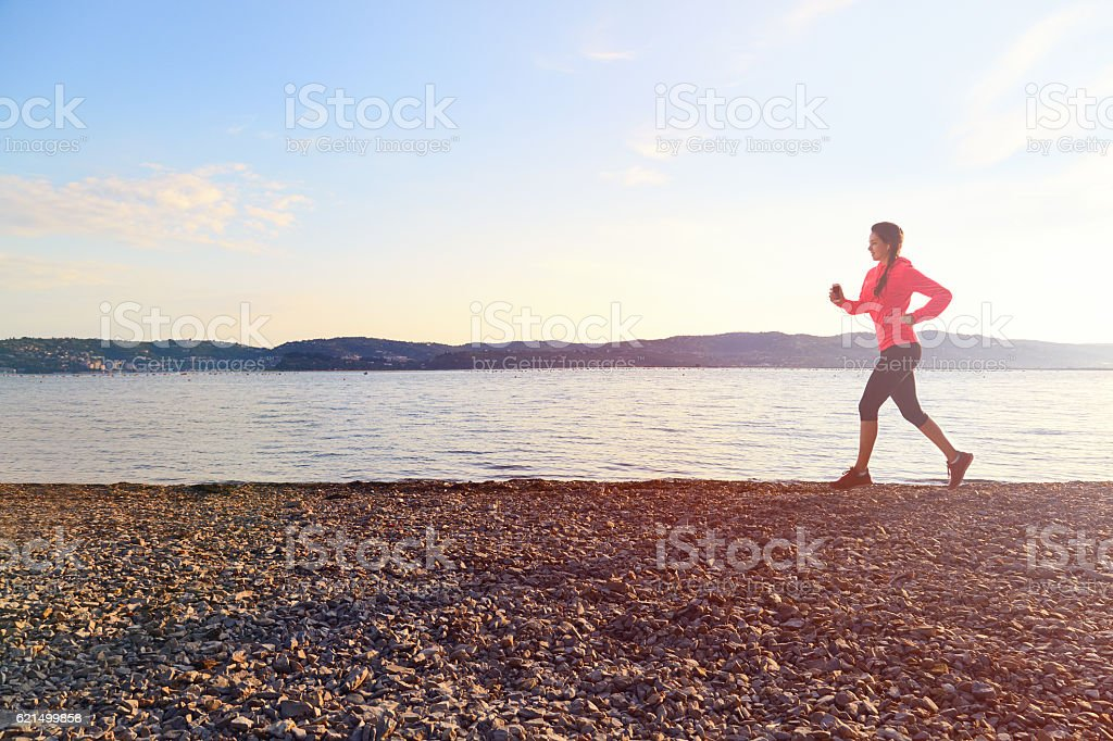 Young fitness woman running outdoors near sea. photo libre de droits