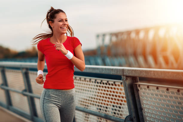 Young fitness woman running outdoors stock photo