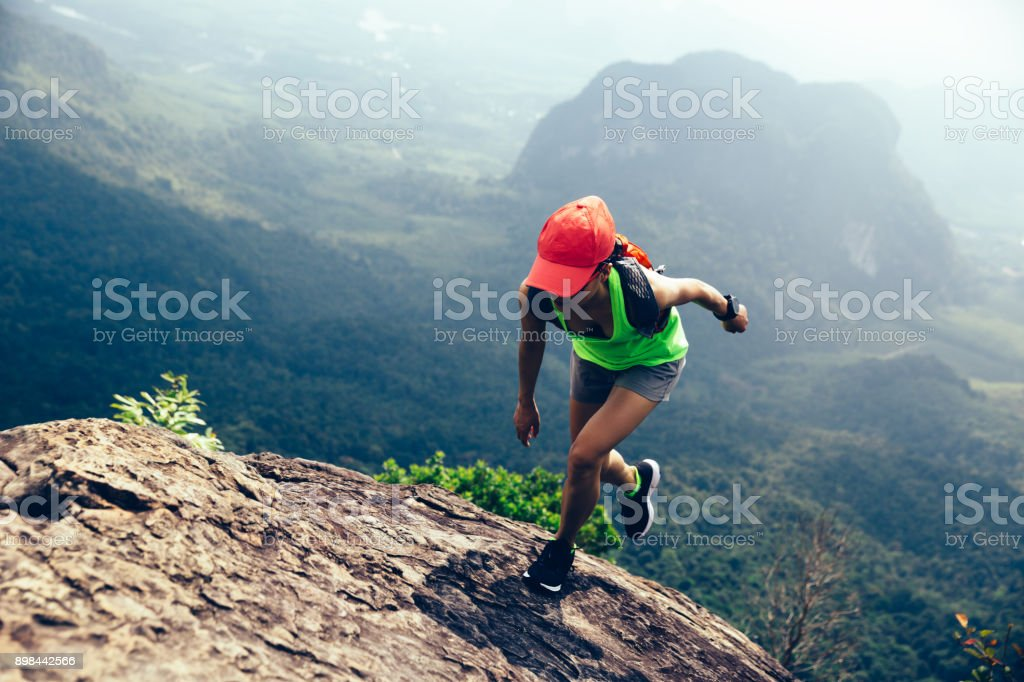 Young fitness woman running up to the mountain top – zdjęcie