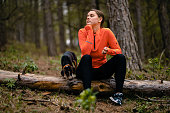 Carefree young woman sitting on a log and resting from a long morning walk in the forest while her puppy playing around
