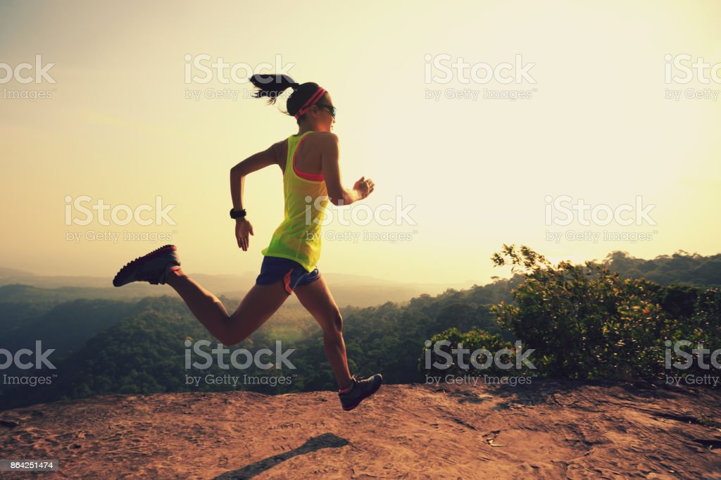 Young fitness woman trail runner running at mountain top royalty-free stock photo