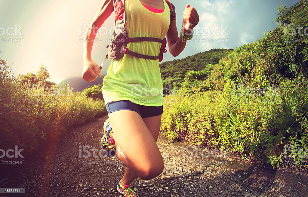 young fitness woman trail runner running on seaside mountain stock photo