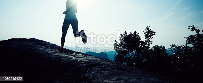 young fitness woman trail runner running to mountain top