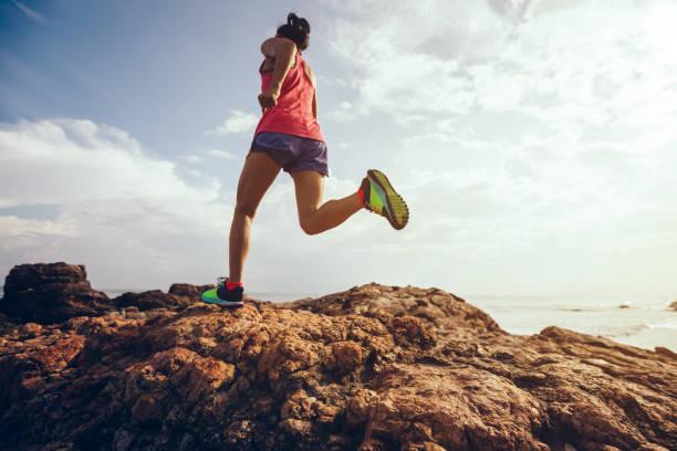 Junge Fitness Frau Trailläufer felsige Berggipfel auf Meer laufen – Foto