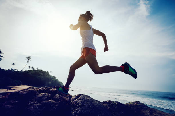 young fitness woman trail runner running to rocky mountain top on seaside - sportsmenka zdjęcia i obrazy z banku zdjęć