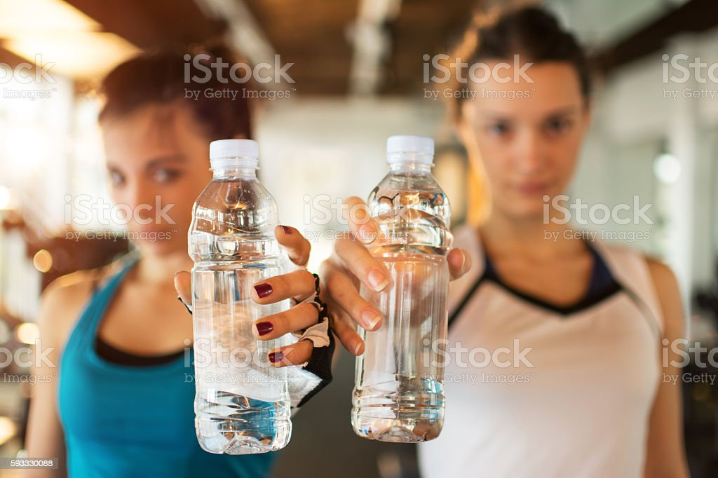 Young fitness women with water bottles. Focus on the bottles. stock photo