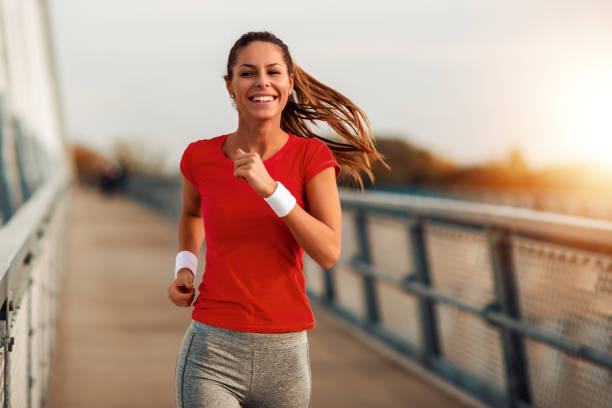 Young fitnesses woman running outdoors stock photo