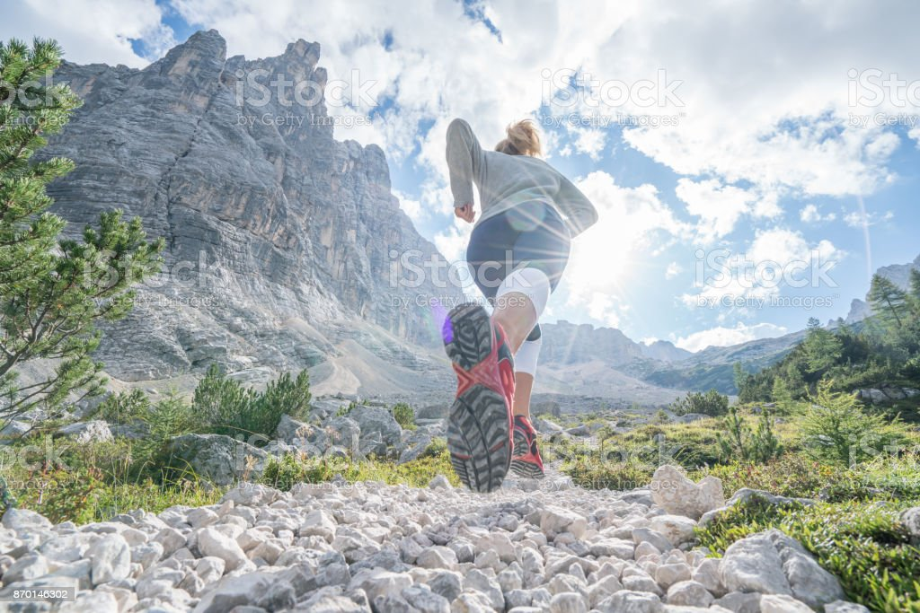 Young fitted woman trail running in the dolomites, Italy stock photo