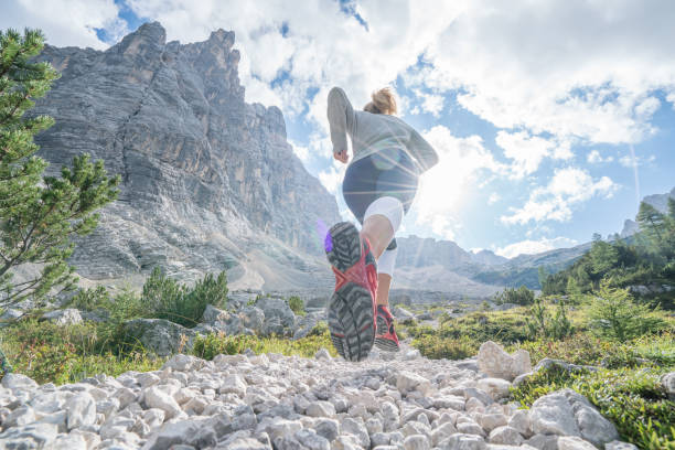 Young fitted woman trail running in the dolomites, Italy Sportive young woman exercising trail running on mountain trail in Alto Adige, Italy. People body conscious and heathy lifestyle concept. endurance stock pictures, royalty-free photos & images