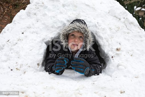 Young five year old boy looking out from his igloo, North Yorkshire, England, UK