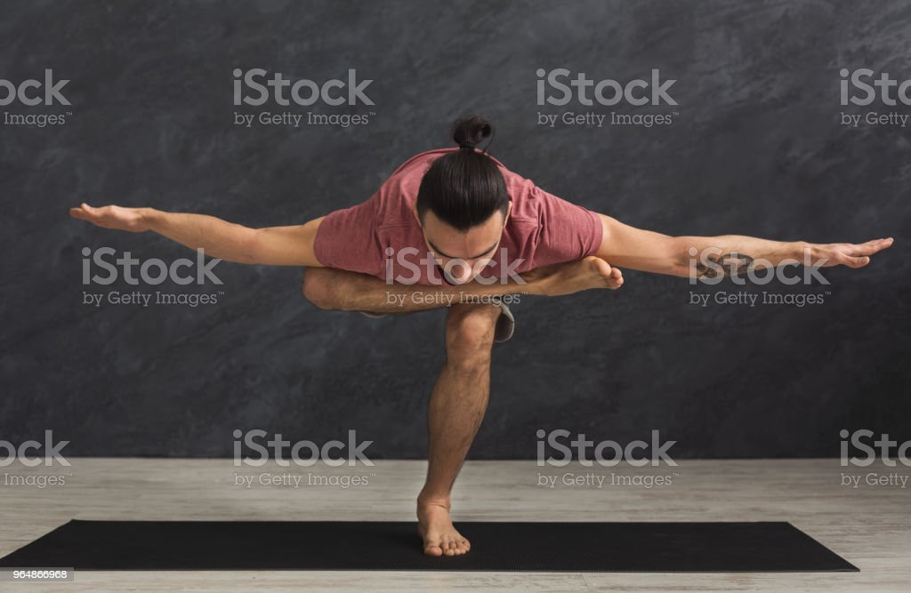 Young flexible man practicing yoga at gym royalty-free stock photo