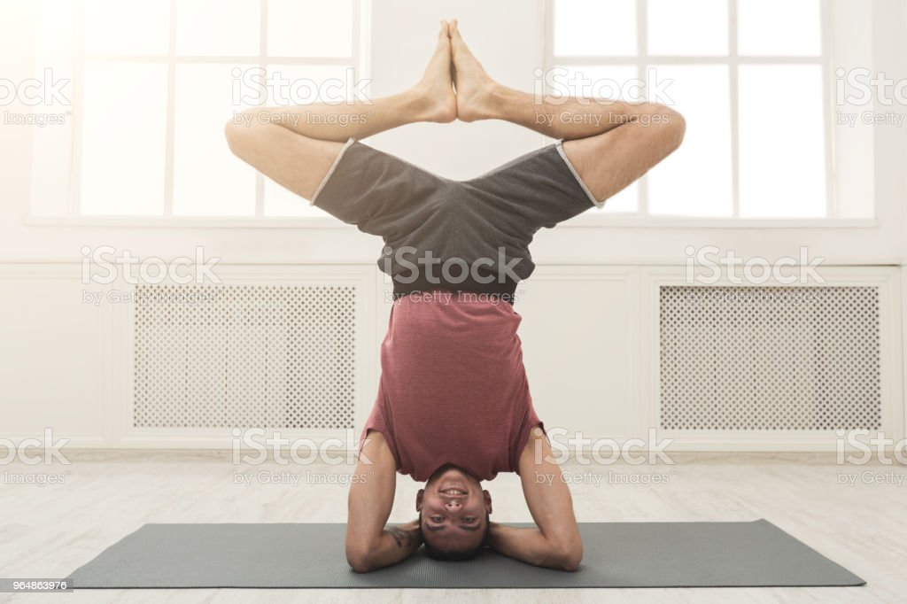 Young flexible man standing on hands royalty-free stock photo