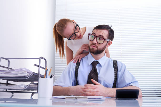 Young flirty woman molesting colleague stock photo