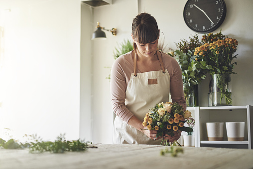 Young florist arranging a mixed flower bouquet in her shop
