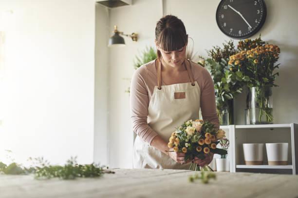 jeune fleuriste arranger un bouquet de fleurs mixtes dans sa boutique - fleuriste photos et images de collection