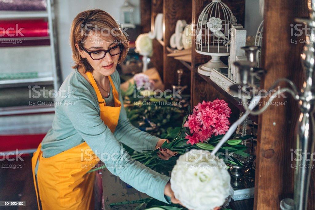 Junge Floristin Vorbereitung einen Blumenstrauß in ihren shop – Foto