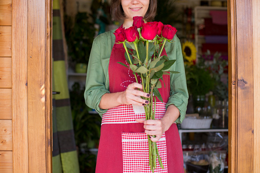 istock Young florist with bouquet of red roses in flower shop doorway 833070598
