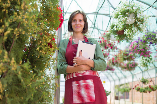 Young florist with digital tablet in plant nursery