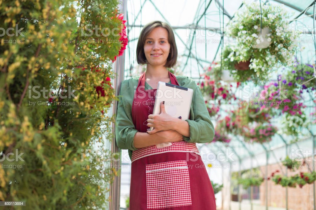 Young florist with digital tablet in plant nursery stock photo