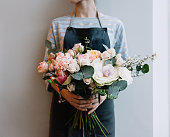 Young florist woman holding freshly made blossoming flower bouquet on the grey wall background.