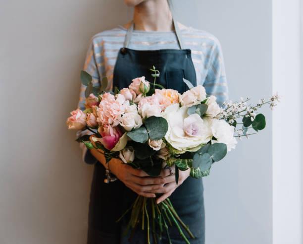 junge floristin frau hält frisch gemacht blühende blumeblumenstrauß auf dem hintergrund der grauen wand. - blumenarrangement stock-fotos und bilder