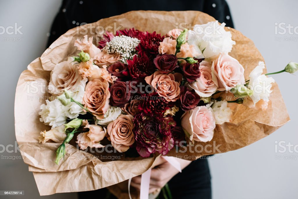 Young Florist Woman Hugging Freshly Made Blossoming Flower Bouquet Of Roseseustoma Chrysanthemums In Brown Colors On The Grey Wall Background Stock Photo Download Image Now Istock