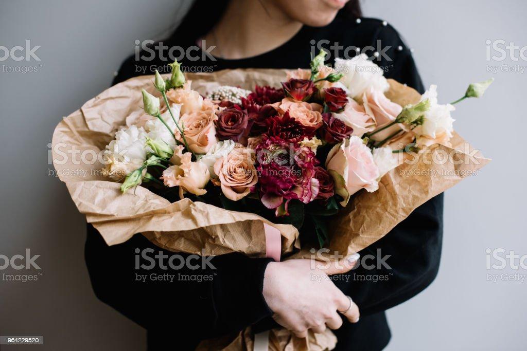 たて抱き若い花屋の女性は灰色の壁の背景に茶色の色のバラトルコギキョウ菊の花の開花の花の花束を作りました 1人のストックフォトや画像を多数ご用意 Istock