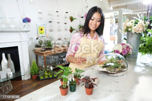 A small business owner of a retail flower shop. An Asian woman florist entrepreneur shopkeeper. She is working close to the checkout counter in her shop, posing with various colorful potted plants,products and merchandize and flower display in the background. Photographed in horizontal format.