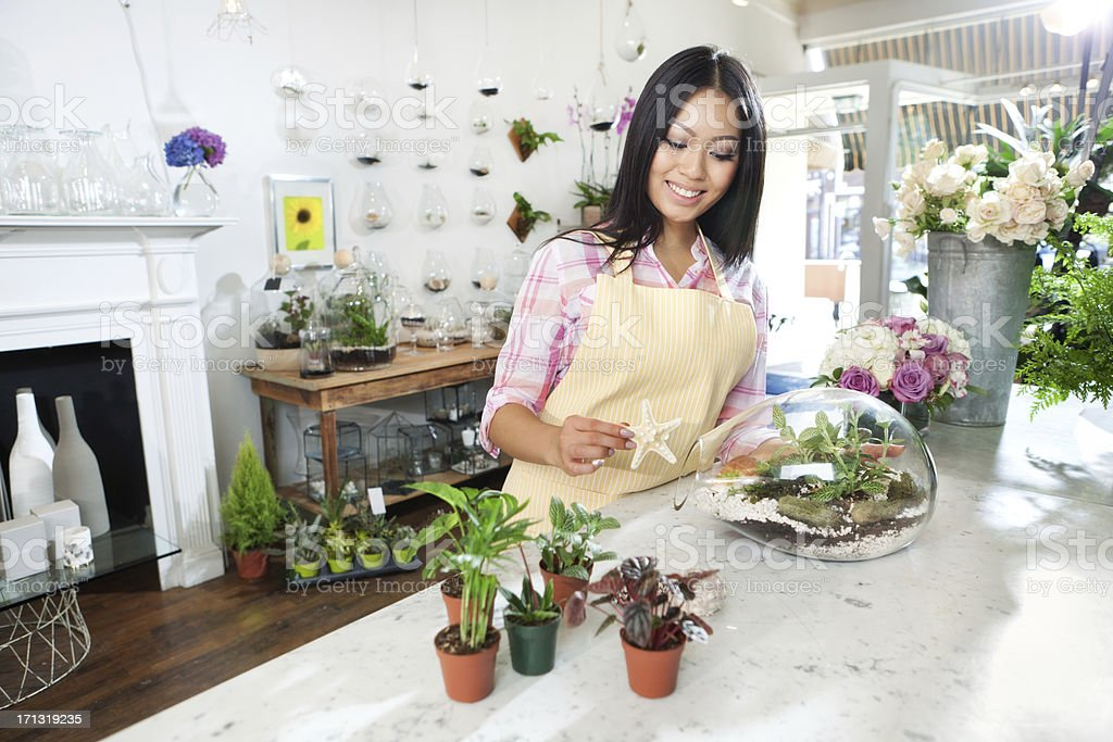 Young Florist Working on Terrarium in Her Retail FLower Shop stock photo